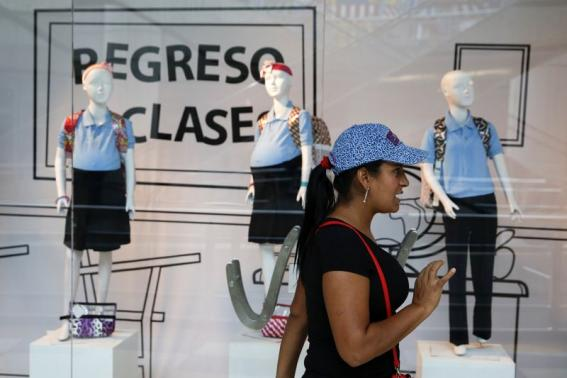A woman reacts in front of a display showing mannequins of pregnant schoolgirls at a shopping mall in Caracas