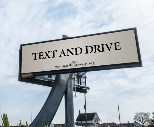 "An image of a ""TEXT AND DRIVE"" billboard from the fictitious Wathan Funeral home"